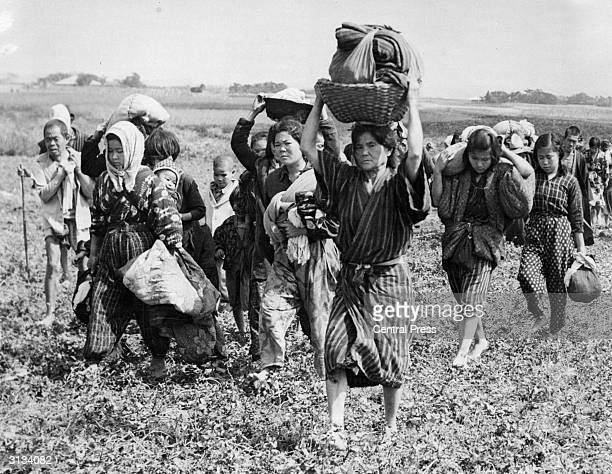 Japanese civilians are forced to pack up their belongings and return to the lowlands of Okinawa in the Ryukyu Islands at the end of World War II....