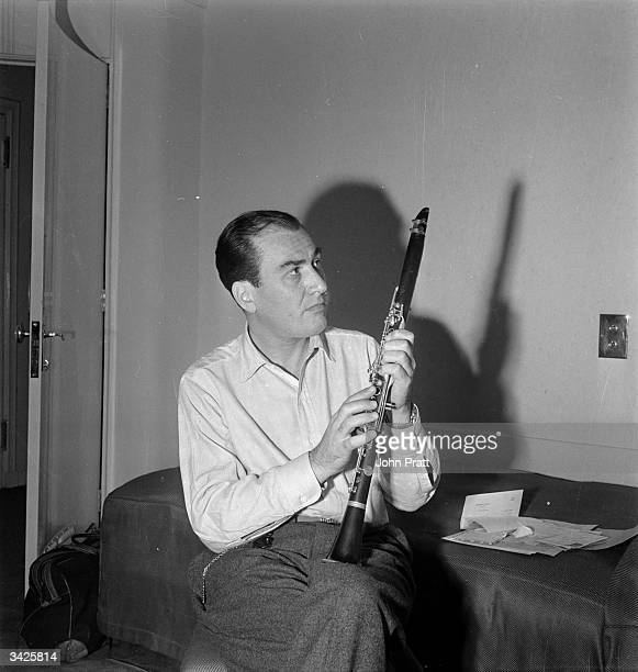 World famous clarinettist Artie Shaw currently staying in London is eventually persuaded to pose with his clarinet at the moment he is more concerned...