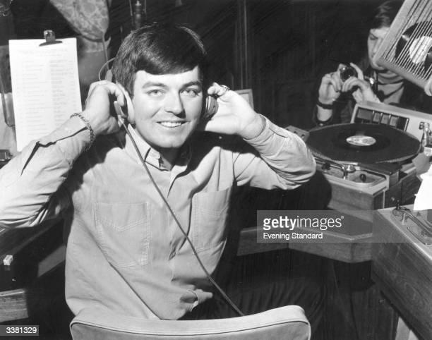 Discjockey Tony Blackburn adjusting his headphones at the opening of BBC Radio's pop music station Radio 1
