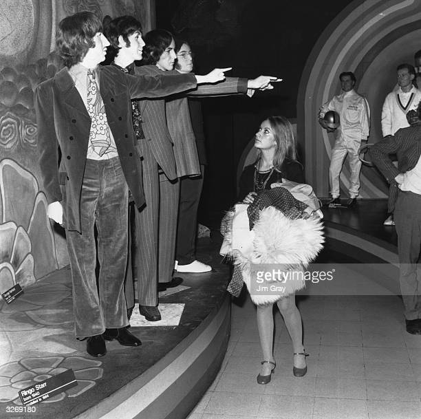 Juliet Simpkins at Madame Tussaud's wax museum in London admires the new figures of pop group the Beatles sculpted by James Butler ARA for display...