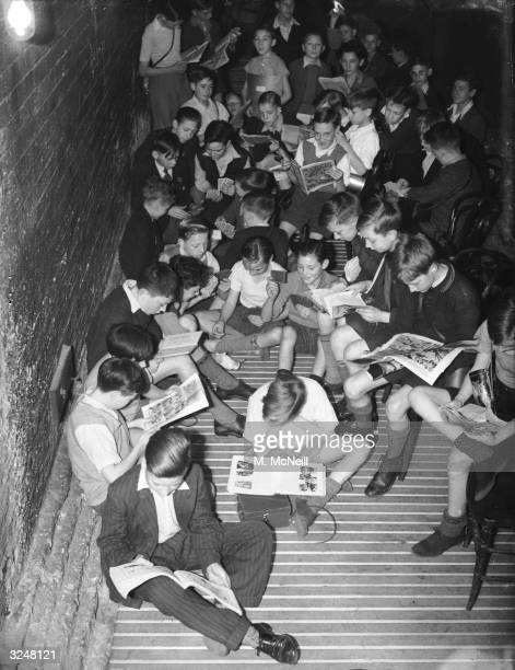 Pupils of Hugh Myddleton School in Clerkenwell London reading their comics in the school shelter during an airraid alarm