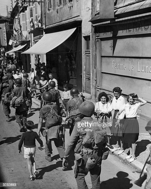 Fulllength image of US troops of the 7th Army 45th Division 157th Infantry Regiment marching through a street while civilians mostly women and...