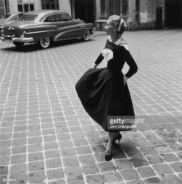 A model twirling a black and white dress with detachable scarf by Lanvin Original Publication Picture Post 7264 Fashion's New Alphabet pub1954