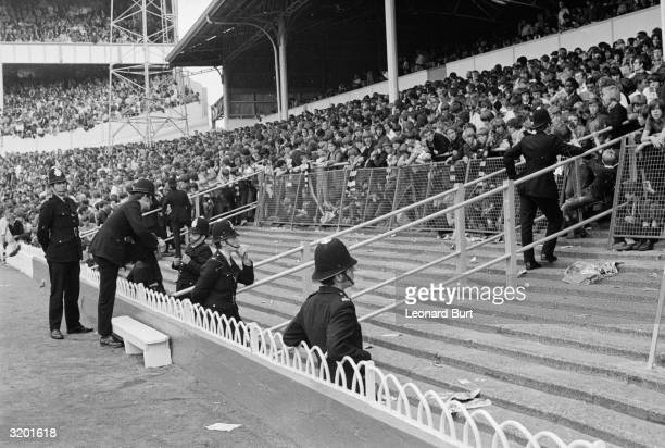 At a football match at White Hart Lane between Tottenham and Liverpool police take precautionary measures to prevent hooligan incidents which have...