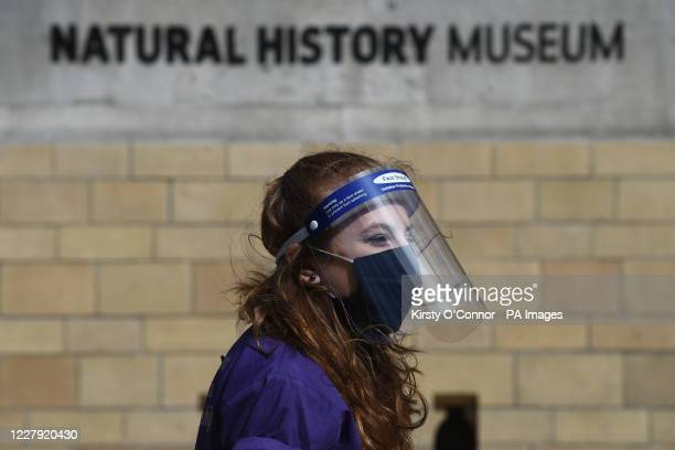 4th TO 5th A member of staff wears PPE at the Natural History Museum in South Kensington, London, as it reopens to the public for the first time...