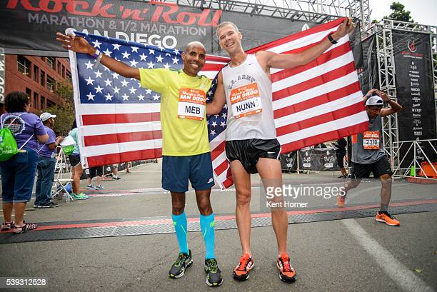 4time Olympian Meb Keflezighi left and Olympian John Nunn pose with the Stars and Stripes flag after finishing the half marathon during the 19th...