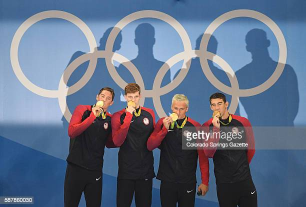US 4x200 freestyle relay team members from left Conor Dwyer Townley Haas Ryan Lochte and Michael Phelps cast large shadows after receiving their gold...