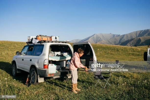 4x4 camping in mountain meadow, woman cooking food - gummistiefel frau stock-fotos und bilder