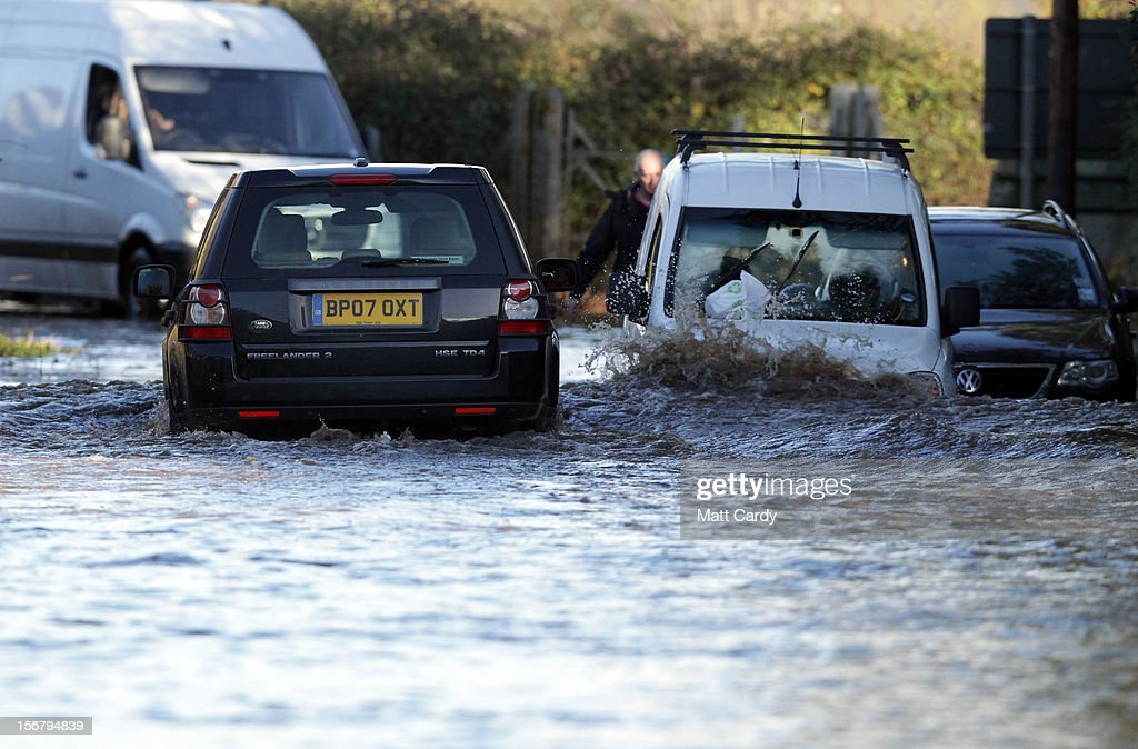 A 4x4 car passes abandoned cars left on a flooded road close to the village of North Curry on November 21, 2012 near Taunton, England. Heavy rain overnight has brought widespread disruption to many parts of the UK particularly in the Somerset and Wiltshire and weather forecasters have warned of more wet and windy weather to come.