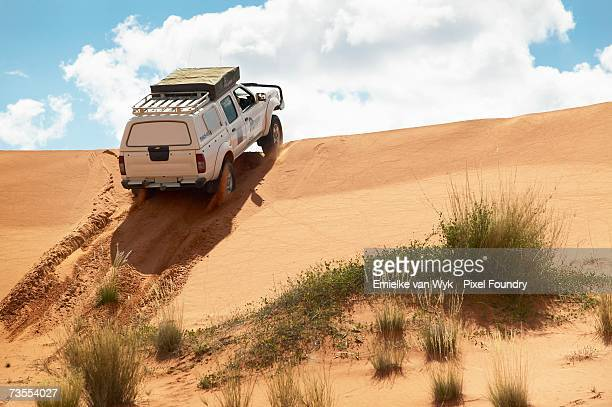 4x4 cruising over a sand dune - low angle - steep stock pictures, royalty-free photos & images