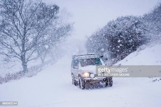 A 4x4 drives across a snowcovered road in the hills above Llangollen north Wales on December 8 as Storm Caroline plunges temperatures across the UK /...