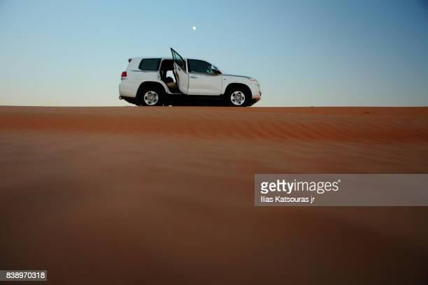 4x4 vehicle atop a desert sand dune