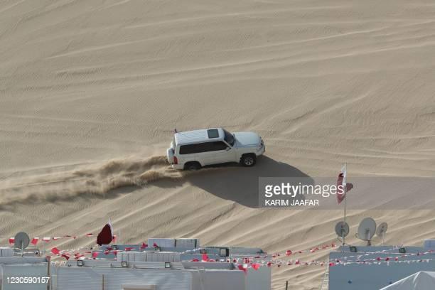 4x4 vehicle drives on a dune of Qatar's Sealine desert, around 63 kilometres south of the capital Doha, on January 8, 2021. - A female 4X4 enthusiast...