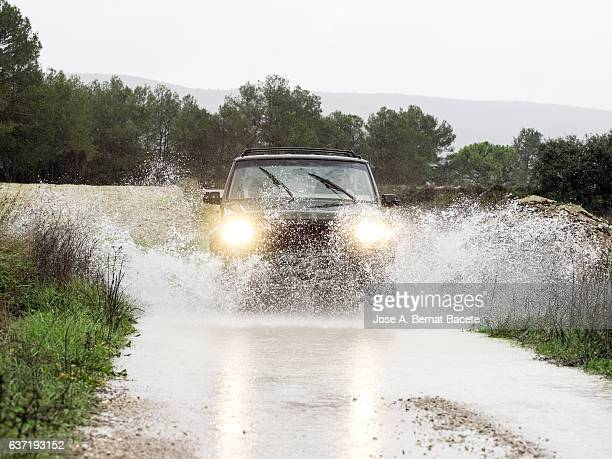 4x4 vehicle on muddy road splashing past a large puddle of rainwater, Spain.