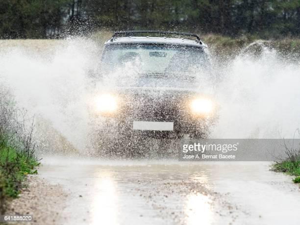 4x4 vehicle on muddy road splashing past a large puddle of rainwater, spain. - 集中豪雨 ストックフォトと画像