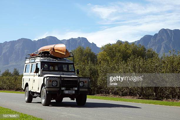 4x4 vehicle stacked with canoe on country road