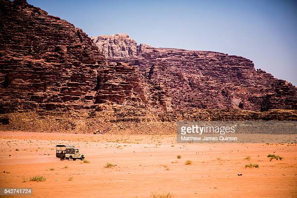 4x4 vehicle traveling in distance over sand in Wadi Rum Jordan with sandstone outcropping in background