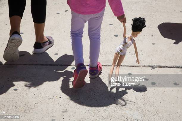 A 4yearold Honduran girl carries a doll while walking with her immigrant mother both released from detention through the 'catch and release' policy...