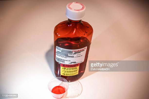 A 500ml bottle of liquid oxycodone an opioid pain relief medication and a dose of 5ml of the solution sit on a table in Washington DC March 29 2019...