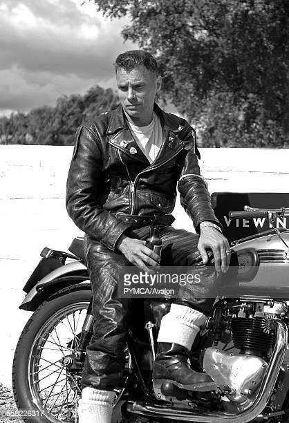 50s style Rocker sitting on a vintage motorbike drinking beer