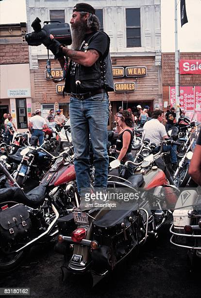 50th Anniversary of the World Famous Sturgis Motorcycle Rally. Bearded man standing on a motorcycle videotaping the rally in Sturgis, South Dakota on...