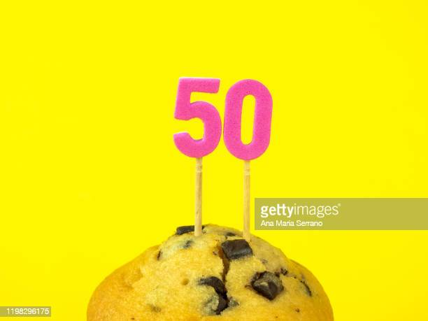 50th birthday candles in a cupcake with chocolate pieces on a yellow background - 50th birthday stock pictures, royalty-free photos & images