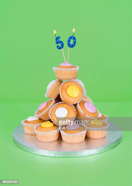 50th birthday candles on pile of fairy cakes - 50th birthday stock pictures, royalty-free photos & images
