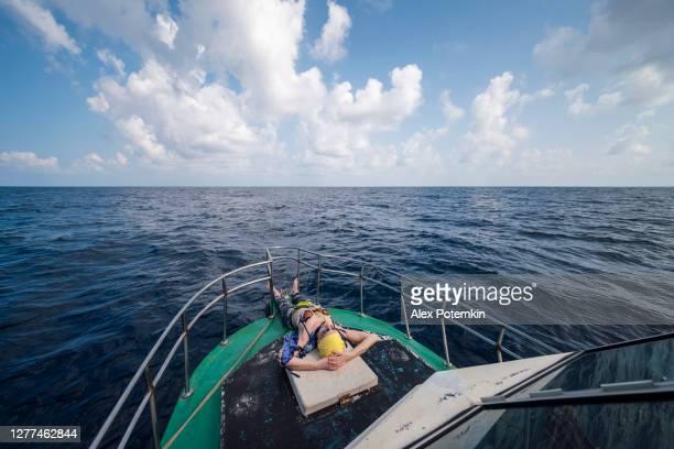una mujer europea activa de 50 años, una turista, se acuesta, descansa y toma el sol en la cubierta de un pequeño barco de pesca frente a la cubierta durante el viaje de pesca en alta mar en sri lanka. - 50-59 years and women only fotografías e imágenes de stock