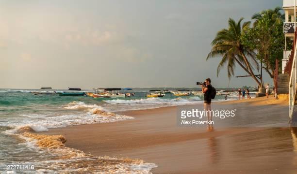 mujer, viajera y fotógrafa de 50 años fotografiando el paisaje marino escénico en la playa tropical de hikkaduwa, sri lanka. - 50-59 years and women only fotografías e imágenes de stock