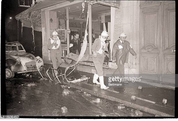 5/11/1968Paris France Red Cross officials and volunteer workers carry wounded student demonstrators past a burned automoblie and a smashed bar window...