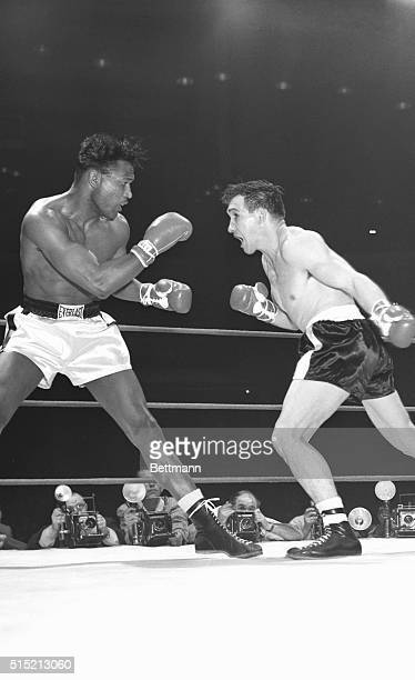 Chicago, IL: As Sugar Ray Robinson backs away, middleweight champion Gene Fullmer charges across the ring to throw a sweeping left in the first round...