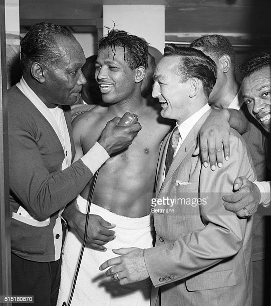 Ray Robinson center surrounded by wellwishers in dressing room is congratulated by Welterwight Champion Carmen Basillo right while Robinson's manager...