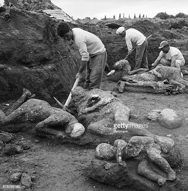 5/1/1961Naples Italy Archaelogical workers extract the mummified bodies of two adults and three children from earthen mold here May 1st These bodies...