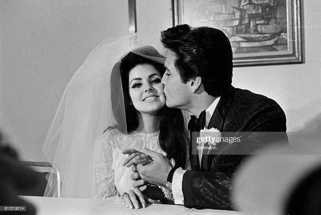Elvis Presley gives his new bride, Priscilla Ann Beaulieu, a kiss following their wedding. The bride wears a large diamond on her finger.