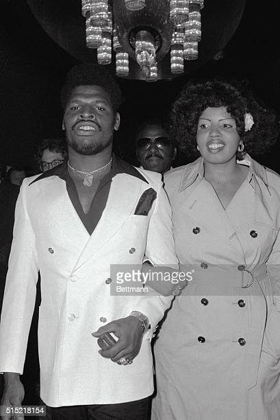 New York, New York- World Heavyweight Champ Leon Spinks arrives at the Americana Hotel, with his wife, Nova, to sign for a rematch with Muhammad Ali....