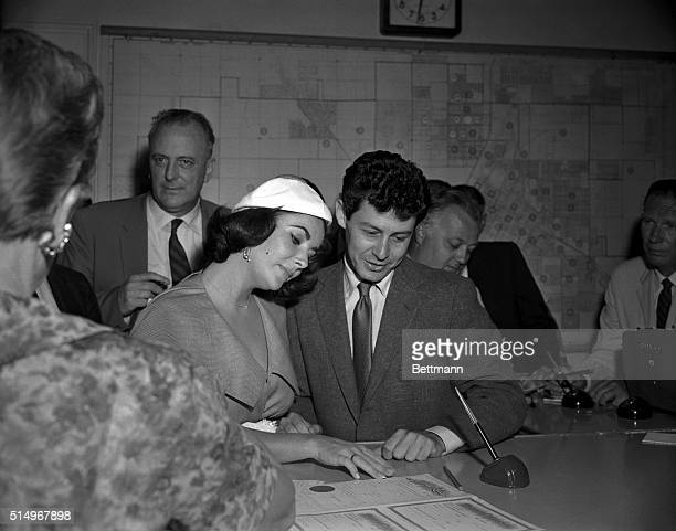Las Vegas, Nevada- Elizabeth Taylor and Eddie Fisher gaze at their marriage license which they obtained right after Fisher was granted a divorce from...