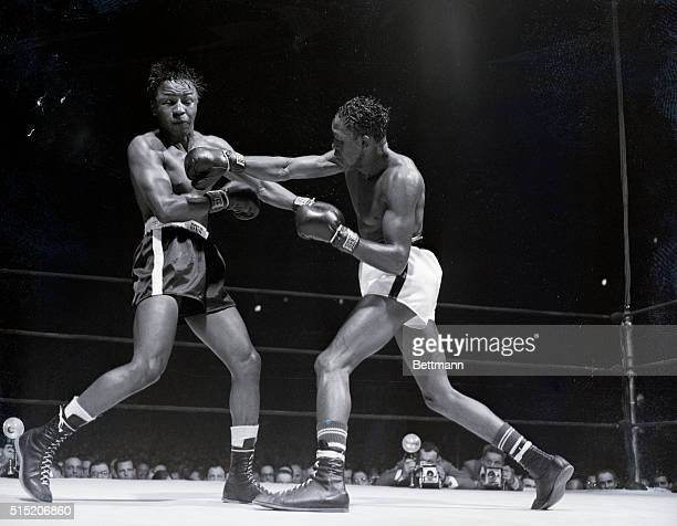 New York, New York- Kid Gavilan slams a hard right to Johnny Bratton's head, closing his eyes and sending his hair flying during their 15-round...