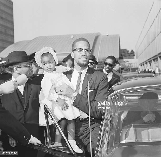 New York, NY: Malcolm X, Militant Black Nationalist movement leader, carries his daughter, Ilyasah, as he enters car at John F. Kennedy International...