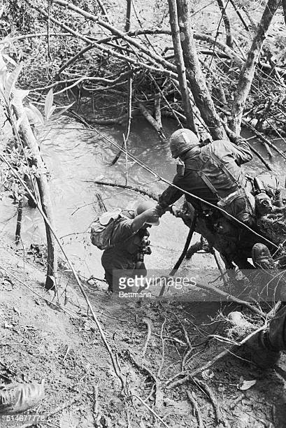 5/24/1965Bien Hoa South Vietnam A paratrooper of the 173rd Airborne helps another paratrooper up a river bank while on patrol One US Army advisor was...