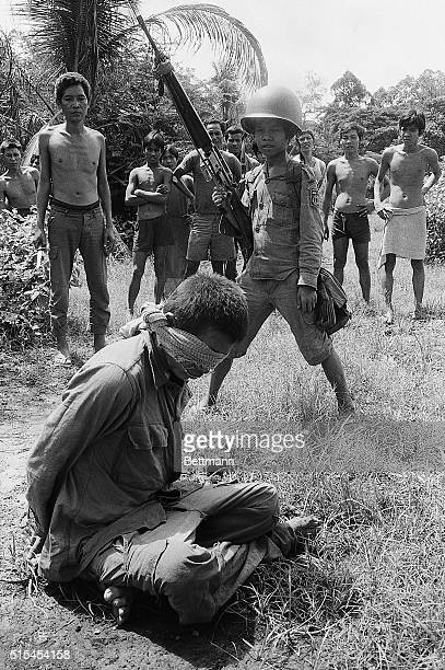 5/24/1973Angkor Chey Cambodia Young Cambodian government soldier stands guard over captured Khmer Rouge after he was captured during a battle 25...