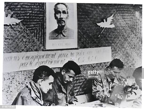 Beneath a portrait of Viet Minh mystery leader Ho Chi Minh festooned with Communist peace doves these captured French soldiers write letters home...