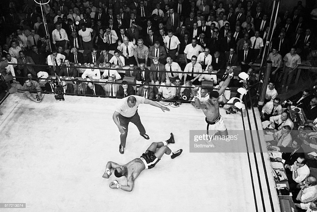 A dramatic overheard photo reveals Sonny Liston spread-eagled on the canvas as heavyweight champion Cassius Clay raises his arms in triumph after a minute of the first round of their title bout here May 25th. Referee is former world heavyweight champion Jersey Joe Walcott. Clay retained his crown after the one minute knockout victory. The bizarre battle immediately triggered nationwide demands for a probe of the fight itself and a demand for federal control of boxing.
