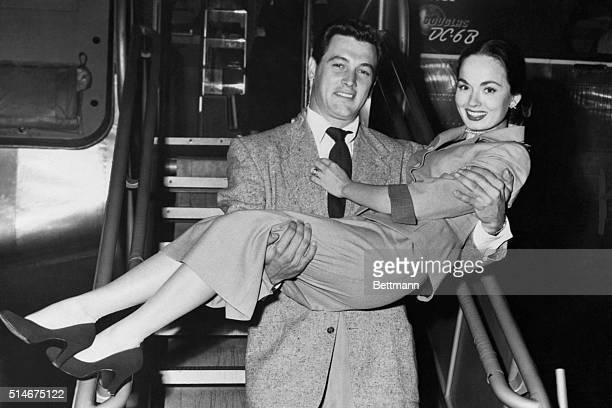 Petite screen star Ann Blyth gets service with a smile from film actor Rock Hudson as they alight from their airliner bringing them to New York from...