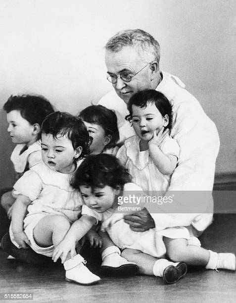 5/28/1935Callender Ontario Honored guest Dr Allan R Dafoe puts his arms around all five of the Dionne quintuplets Marie Emelie Cecile Annette and...