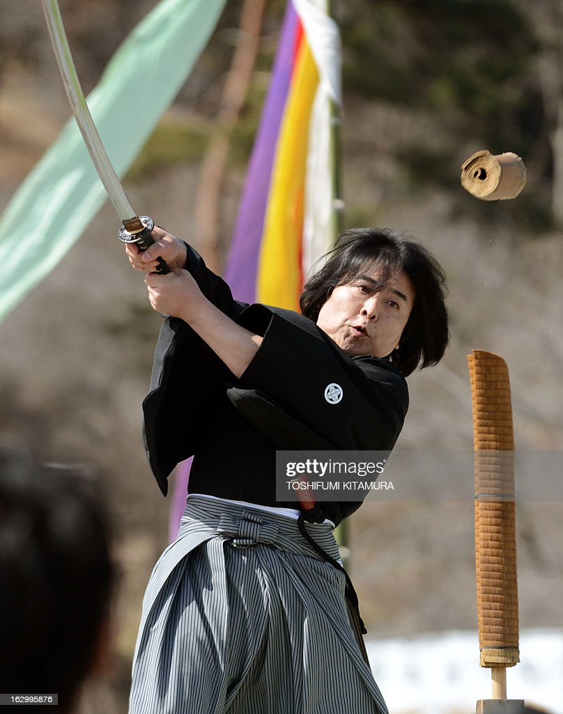 52-year-old Katsuihiro Akaiwa cuts the 'Tatami-mat stick' while perfroming his Genryu-style skills of 'Iai-batto-jyutu,' or techniques for engaging Japanese sword as a part of the event of the 'Hi-watari', or fire walking ceremony, to herald the coming of spring at the Fudoji temple in Nagatoro town, Saitama prefecture, on March 3, 2013. Thousands of people watched and joined the fire walking ritual to purify the mind and body and to pray for safety.