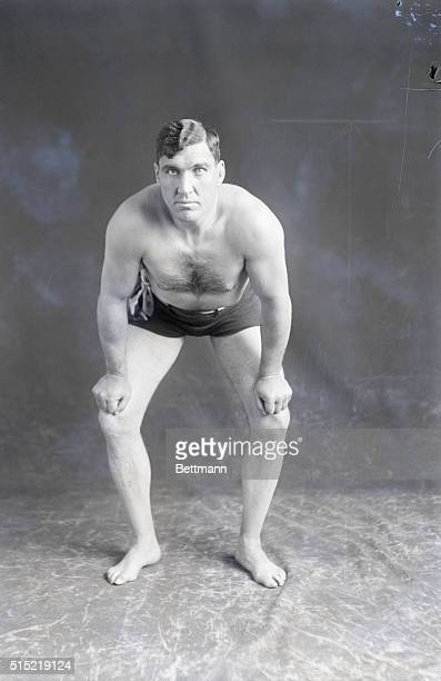 Jess Willard exercising. He is shown bent over in a pose.