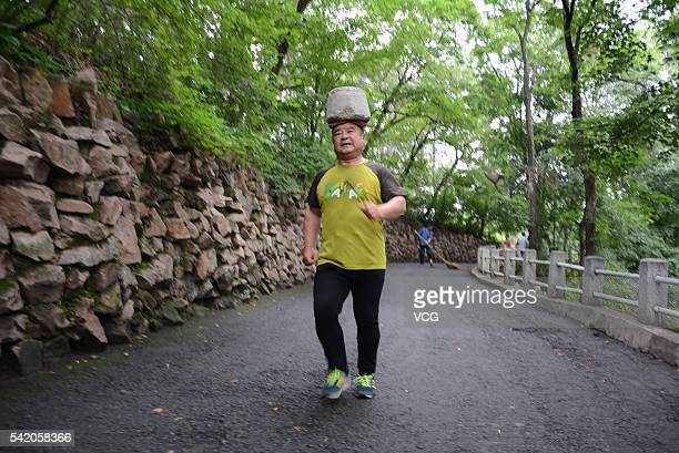 A 54yearold man Cong Yan heads a 40kilogram stone while running at Beishan Park on June 22 2016 in Jilin Jilin Province of China Cong Yan a 54yearold...