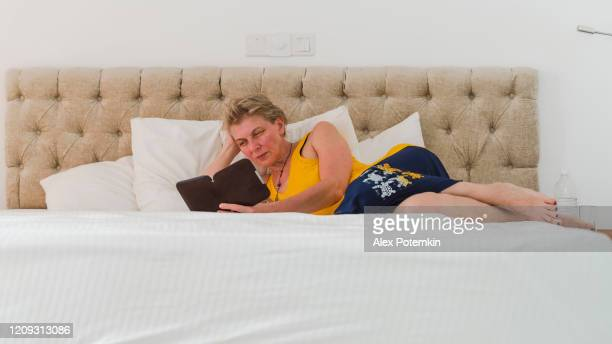 55-years-old attractive caucasian white woman reading an electronic book when she lies on a bed in a bright and clean modern hotel room. - 55 59 years stock pictures, royalty-free photos & images