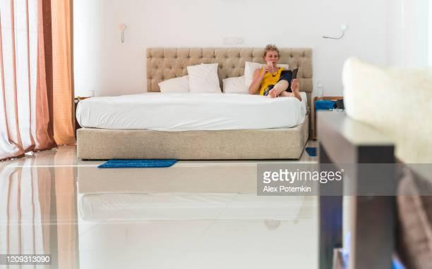 mujer blanca caucásica de 55 años que lee un libro electrónico cuando se sienta en una cama en una habitación de hotel moderna y luminosa y luminosa. - 50-59 years and women only fotografías e imágenes de stock