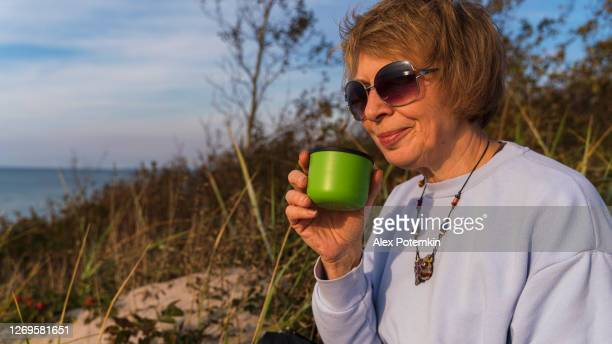 55-years-old mature active, attractive woman sitting on a sandy dune which grew with dogrose, in the sunny autumn day, and drinking a tea from a green thermos. - 55 59 years stock pictures, royalty-free photos & images